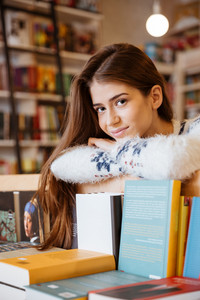 Portrait of a happy smiling female student leaning on the book shelf