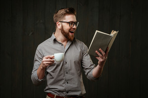 Portrait of a happy smiling man in eyeglasses reading book and holding cup of coffee isolated on a black wooden background