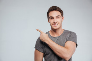 Portrait of a happy smiling man pointing finger away at copyspace isolated on a white background