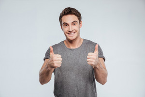 Portrait of a happy smiling man showing two thumbs up isolated on the gray background