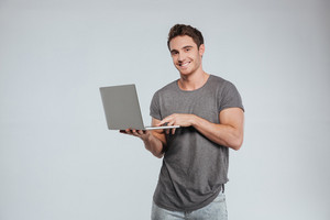 Portrait of a happy smiling man using laptop and looking at camera over white background