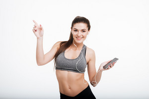 Portrait of a happy smiling sports woman listening music on her mobile wearing earphones and pointing finger away isolated on a white background