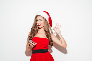 Portrait of a happy smiling woman in red santa claus dress and hat holding mobile phone and showing okay gesture isolated on the white background