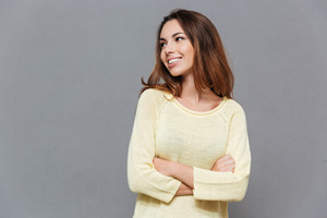 Portrait of a happy smiling woman in sweater with hands crossed looking away isolated on the gray background