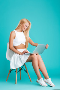 Portrait of a happy smiling woman using laptop computer while sitting on chair isolated on the blue background