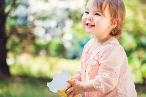 Portrait of a happy toddler girl playing outside with a big smile