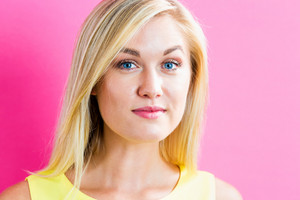 Portrait of a happy young blonde woman on a pink background