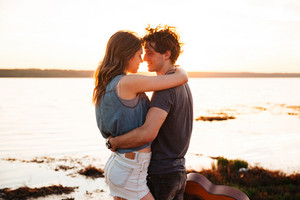 Portrait of a happy young couple hugging and kissing at the seaside