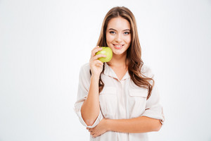 Portrait of a happy young girl holding green apple isolated on a white background
