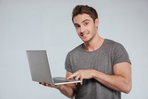 Portrait of a happy young man standing and holding laptop over white background