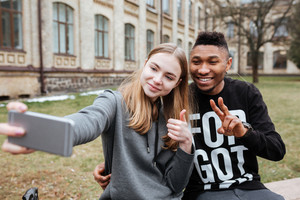 Portrait of a happy young teenagers couple taking selfie outdoors at the city campus