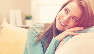 Portrait of a happy young woman smiling in her living room