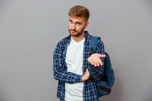 Portrait of a hipster man standing with open palm and looking at camera isolated on a gray background