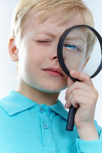 Portrait of a kid looking through magnifying glass