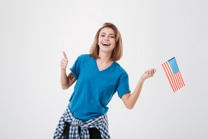Portrait of a laughing casual girl holding usa flag and showing thumbs up isolated on a white background