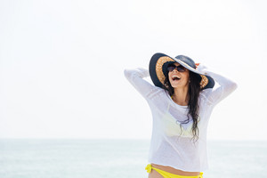 Portrait of a laughing young woman wearing beach hat and bikini outdoors