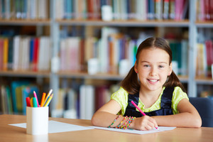 Portrait of a lovely girl drawing with pencil in library