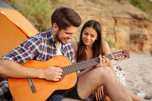 Portrait of a man playing guitar for his girlfriend sitting at the camping tent