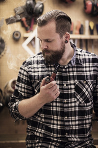 Portrait of a man smoking pipe in wood workshop