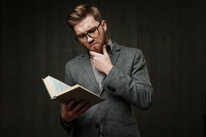 Portrait of a pensive bearded man in eyeglasses reading book isolated on the black wooden background