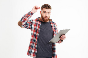 Portrait of a pensive bearded man in plaid shirt holding clipboard and scratching head with pencil over white background