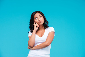 Portrait of a pensive pretty asian girl thinking about something isolated on the blue background