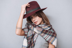 Portrait of a playful pretty woman in scarf taking off her hat and looking at camera isolated on the gray background