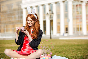 Portrait of a pretty red head girl holding cup of tea while having a picnic in park