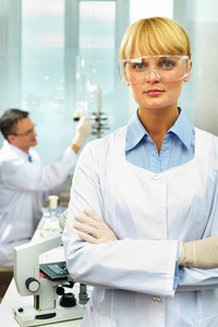Portrait of a pretty scientist looking at camera against her working colleague