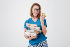 Portrait of a pretty smiling girl student holding pile of books and biting apple isolated on the white background