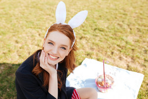 Portrait of a pretty young girl with long red hair wearing bunny ears and having easter picnic outdoors