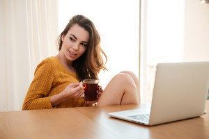 Portrait of a pretty young woman sitting at the table with cup of tea and laptop at home