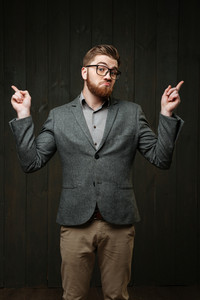 Portrait of a puzzled bearded man in eyeglasses and suit pointing fingers away isolated on the black wooden background