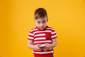 Portrait of a sad little boy holding mobile phone and looking at camera isolated over orange background