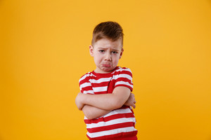 Portrait of a sad upset little boy crying isolated over orange background