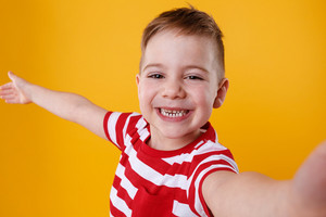 Portrait of a satisfied cheerful little boy holding mobile phone and making selfie isolated over orange background