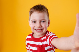 Portrait of a satisfied cute little boy holding mobile phone and making selfie isolated over orange background