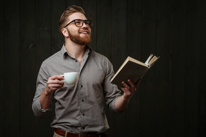 Portrait of a satisfied young man looking up while holding open book and cup of coffee isolated on a black wooden background