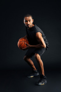 Portrait of a serious african sports man playing in basketball isolated on a black background