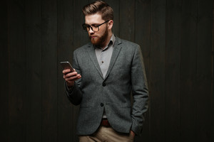 Portrait of a serious bearded man in casual suit standing with mobile phone isolated on the black wooden background