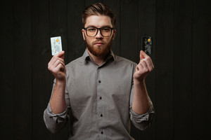 Portrait of a serious bearded man in eyeglasses holding credit cards and looking at camera isolated on the black wooden background