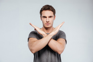 Portrait of a serious casual man showing crossed arms in a stop gesture isolated on the gray background
