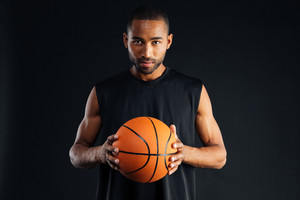 Portrait of a serious confident basketball player isolated on a black background
