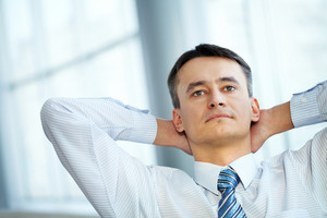 Portrait of a serious mature businessman sitting with his hands behind head