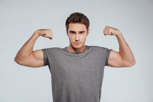 Portrait of a serious strong man flexing both biceps and looking at camera isolated on the gray background