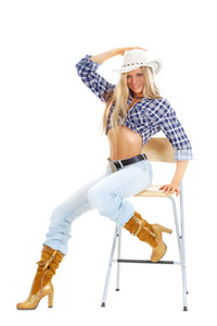 Portrait of a sexy woman in American cowgirl clothing posing on a chair