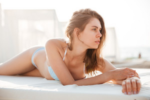 Portrait of a sexy young brunette woman in bikini lying on bed