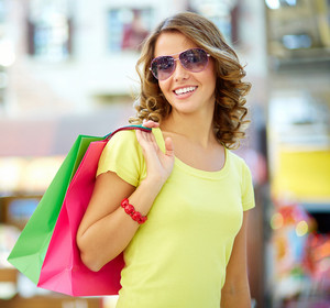 Portrait of a shopping young woman wearing cool sunglasses