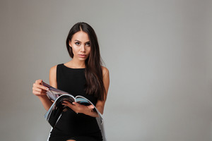 Portrait of a smart beautiful woman holding magazine over gray background