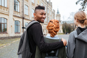 Portrait of a smiling afro american man student with backpack walking outdoors with his friends